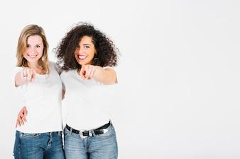 Smiling women pointing at camera