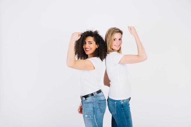 Smiling women showing biceps