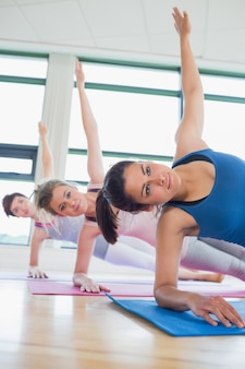 Smiling women in side plank yoga pose