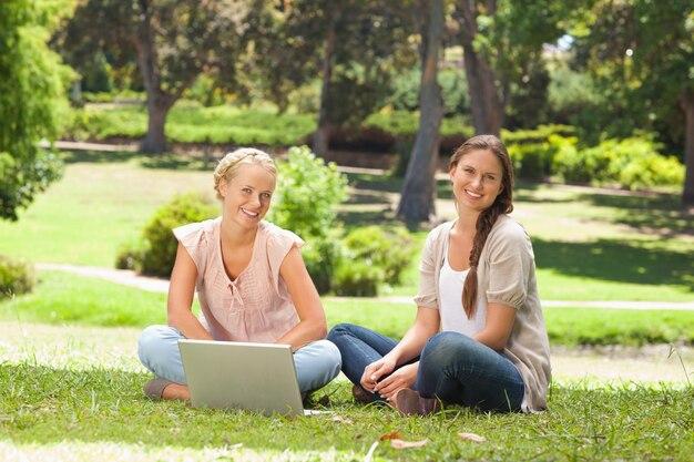 ラップトップで公園に座っている笑顔の女性
