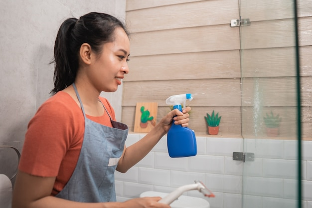 Smiling women spray using a bottle sprayer and hold the window wipers while cleaning the glass in the bathroom