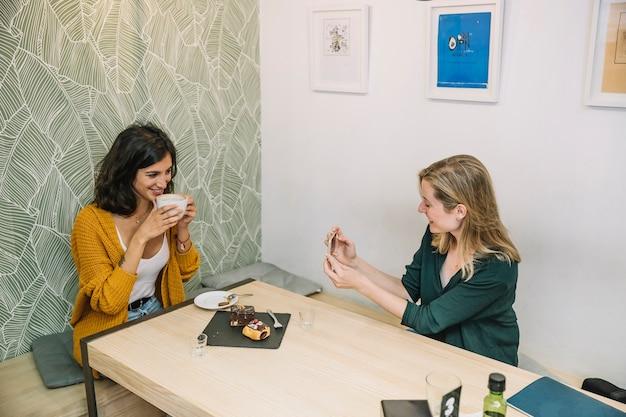 Smiling women taking photos in cafe