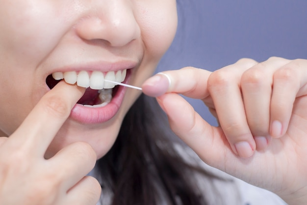 Smiling women use dental floss white healthy teeth