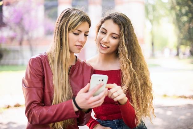 屋外で携帯電話を使用して笑顔の女性