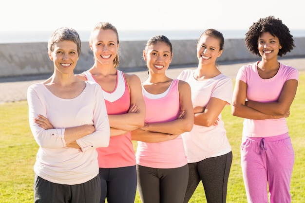 Smiling women wearing pink for breast cancer with arms crossed