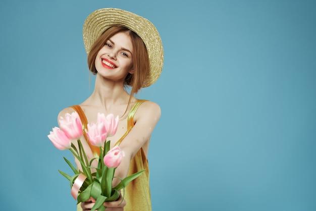 帽子の春の休日に花束と笑顔の女性