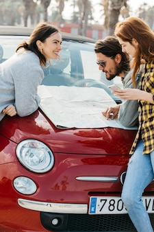 Smiling women with smartphone near man looking at map on car hood