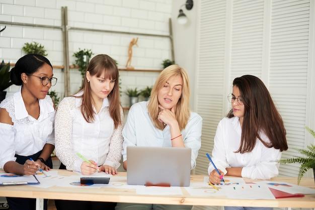 웃는 여성들은 현대적인 사무실에서 함께 일합니다. 페미니즘. 사무실에 서서 비즈니스 서류를 논의하는 전문적인 웃고 있는 비즈니스 여성.