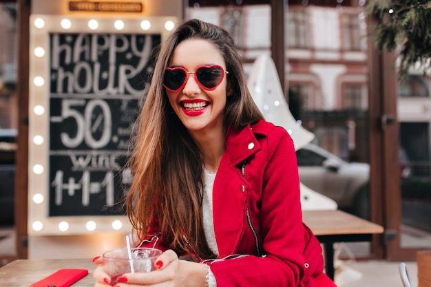 Smiling wonderful girl in stylish sunglasses spending weekend morning in outdoor cafe