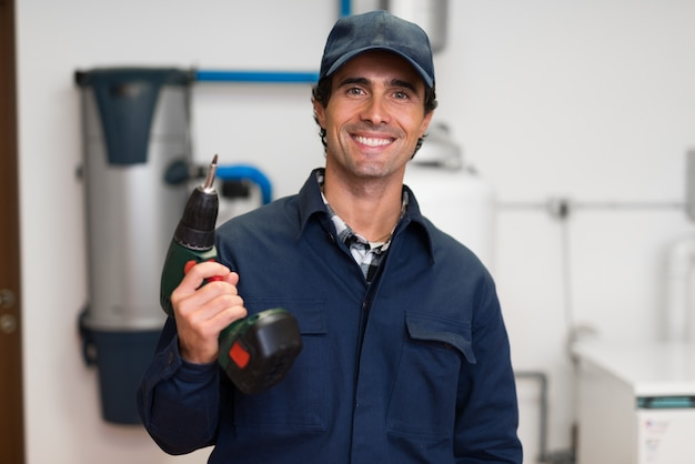 Smiling worker holding a cordless screwdriver