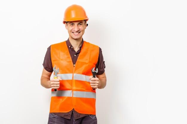 保護された制服と分離された保護用のヘルメットで笑顔の労働者