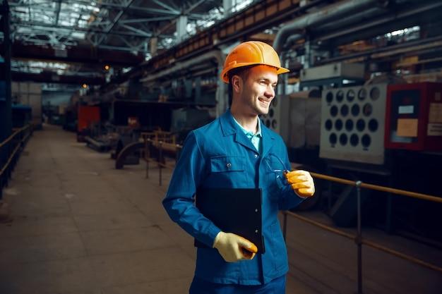 유니폼과 안전 헬멧을 쓴 웃는 작업자는 노트북, 공장 바닥, 공장을 보유하고 있습니다. 산업 생산, 금속 공학, 동력 기계 제조