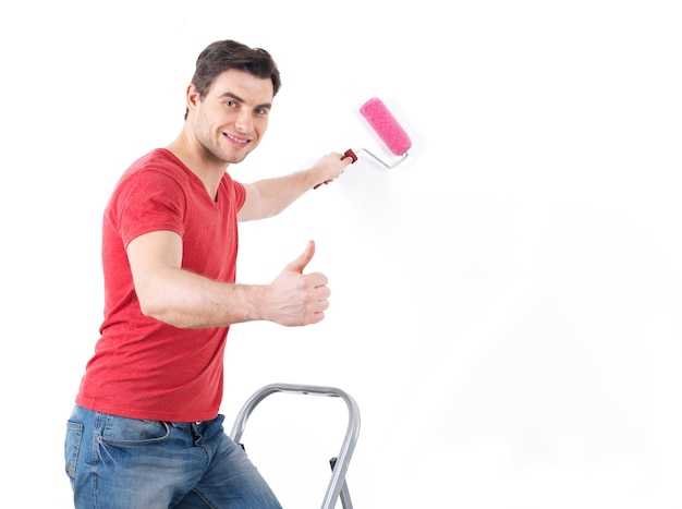Smiling worker painter with brush showing thumbs up sign isolated on white