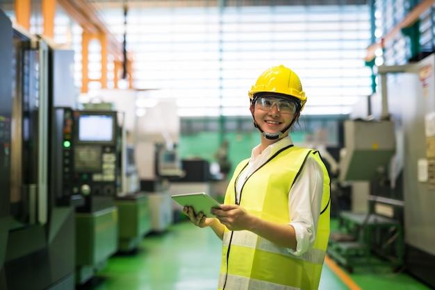 태블릿을 사용하여 웃는 작업자와 공장의 트랜지스터 마이크로칩 기계를 봅니다.