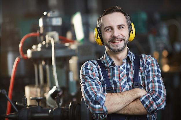 Smiling worker wearing earmuffs