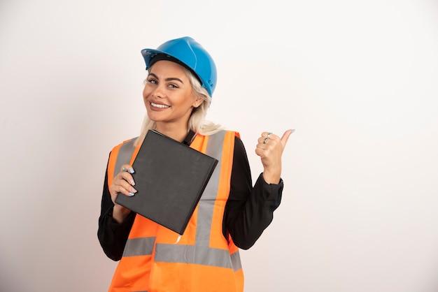 白い背景に親指を立てるノートブックと笑顔の労働者。高品質の写真