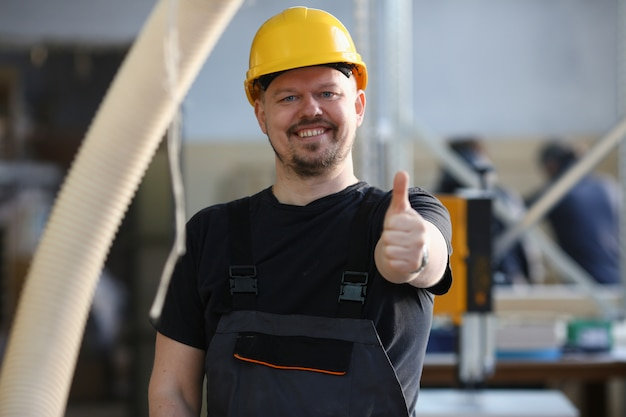 Smiling worker in yellow helmet show confirm sign with thumb up at arm portrait. manual job diy inspiration joinery startup idea fix shop hard hat industrial education profession career concept