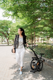 Smiling working woman walks on her folding bike through the park