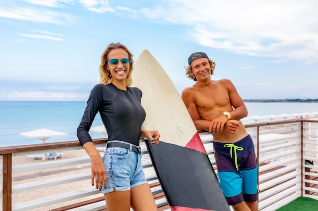Smiling young active couple surfers relaxing on the beach after sport with surfboard. healthy lifestyle. extreme water sports