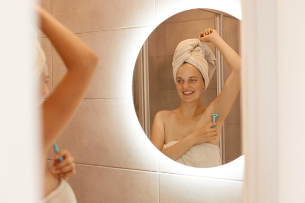 Smiling young adult girl shaving armpit in bathroom, holding shaver in hand, looking at the mirror reflection with happy expression, being wrapped in white towel, doing women's procedures.