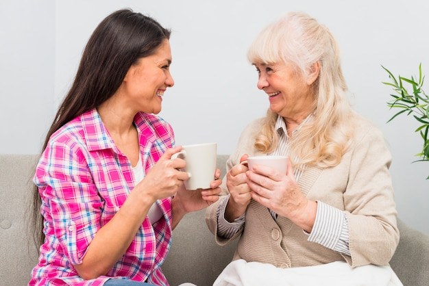 Smiling young adult and senior mother holding cup of coffee looking at each other