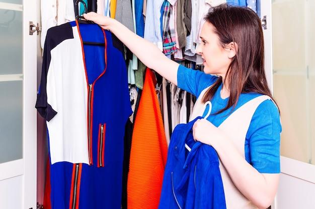 春夏のドレスでワードローブをチェックして片付けを探している若い大人の女性の笑顔。服を注文するコンセプト