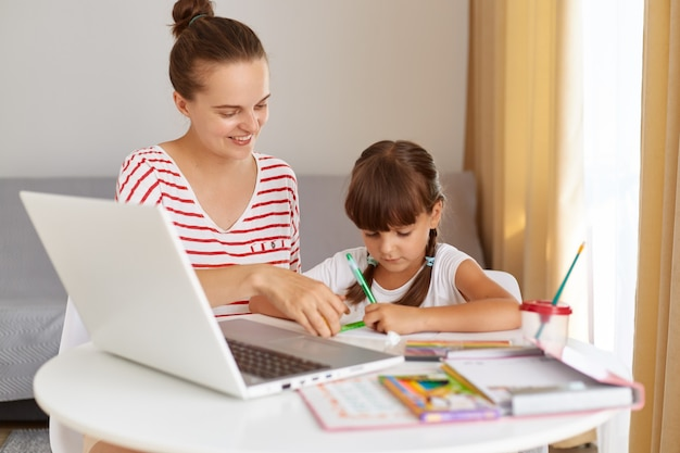 Smiling young adult woman wearing striped casual clothing helping her little daughter to do homework, distance education during quarantine, online lesson.