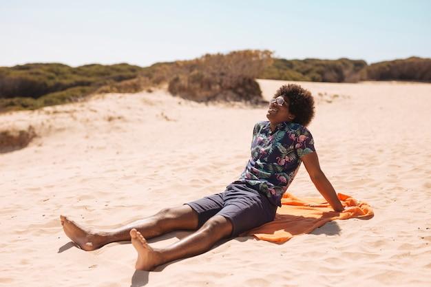 Улыбающийся молодой афроамериканец человек, наслаждаясь солнцем