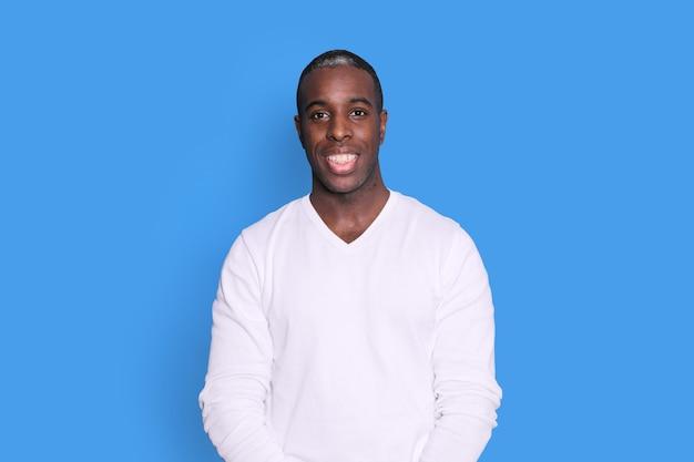 파스텔 파란색 배경 스튜디오 초상화에 고립 된 포즈 캐주얼 흰색 스웨터에 젊은 아프리카 계 미국인 남자 남자를 웃 고. 사람들이 성실한 감정 라이프 스타일 개념. 복사 공간을 모의합니다. 카메라를 찾고 있습니다.
