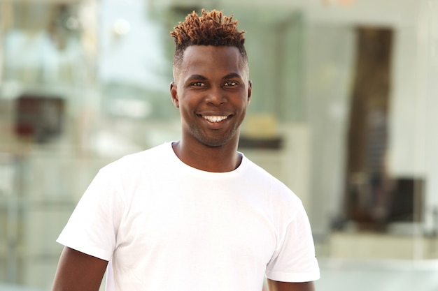 Smiling young african american man standing outside in the city