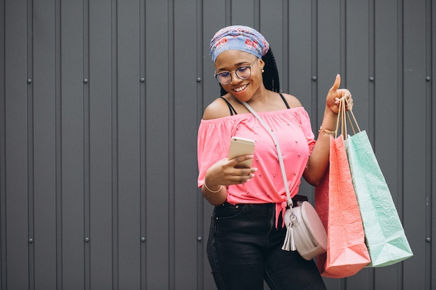 Smiling young african american woman holding phone and shopping bags at he gray wall