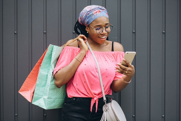 Smiling young african american woman holding phone and shopping bags