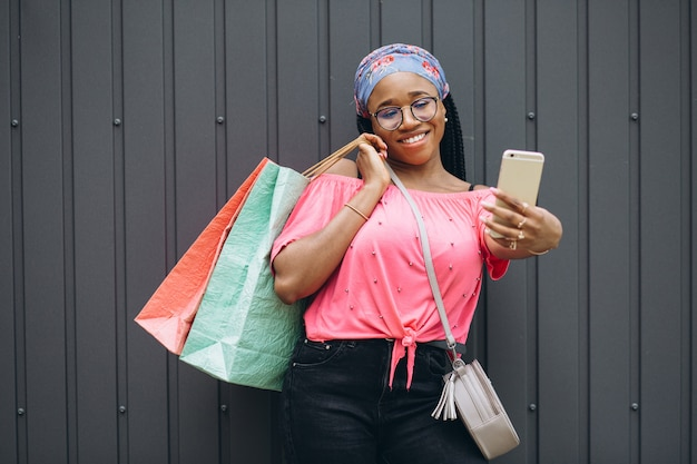 Smiling young african american woman holding shopping bags and make selfie at the gray wall