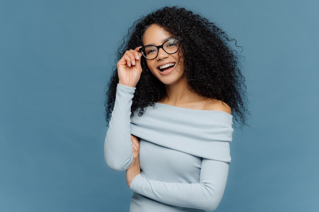 Smiling young african american woman touches frame of glasses
