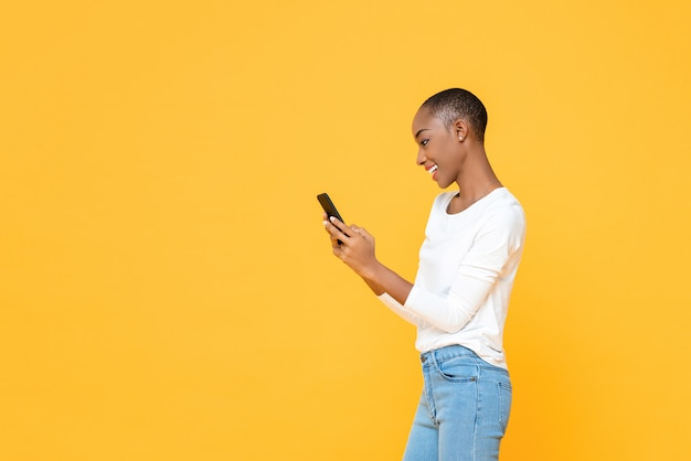 Smiling young african american woman using smartphone  isolated on yellow wall