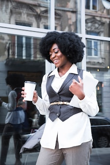 Smiling young african businesswoman holding takeaway coffee cup and digital tablet in hand