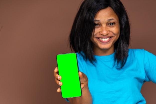 웃고 있는 젊은 아프리카 여성, 그녀의 전화를 들고 빈 녹색 화면을 보여주고, 전화에 집중