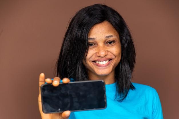 웃고 있는 젊은 아프리카 여성, 그녀의 전화를 들고 빈 화면을 보여주고, 전화에 집중
