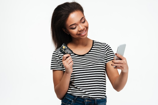 Smiling young african lady using phone and holding debit card.