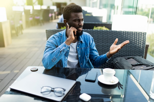 Smiling young african man drinking coffee and talking on mobile phone while sitting in cafe