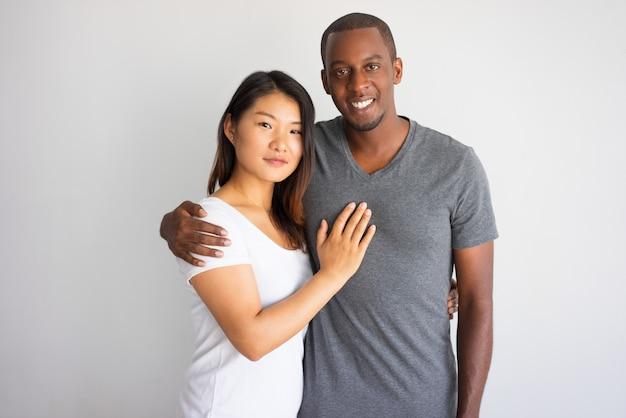 アジアのガールフレンドを抱擁している若いアフリカの男を笑っている。