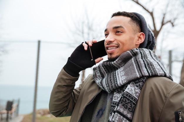 Улыбающийся молодой африканский человек разговаривает по телефону.