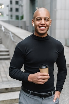 Smiling young african man wearing wireless headphones standing in the city street, looking at front