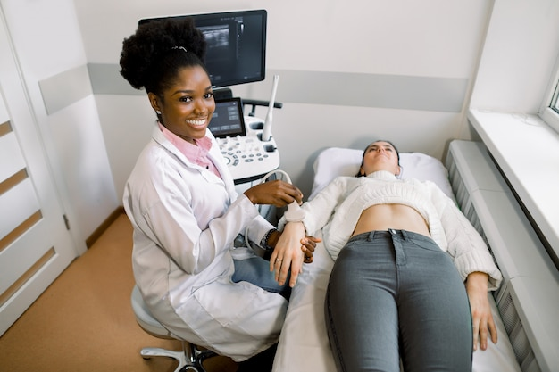 Smiling young african woman doctor using ultrasound probe on the wrist of young caucasian woman patient