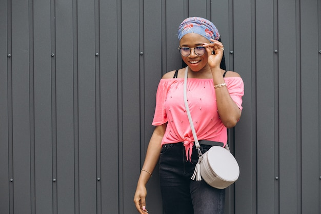 Smiling young african woman in a glasses with bag posing against gray wall