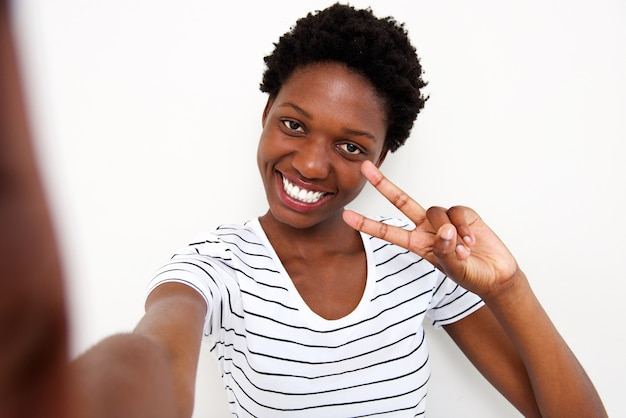Smiling young african woman making peace sign selfie against white background