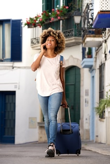 Smiling young african woman traveling with bag and mobile phone on street