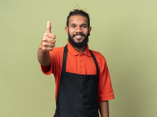 Sorridente giovane barbiere afroamericano che indossa l'uniforme che mostra il pollice in su