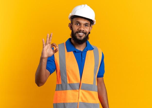 コピースペースでオレンジ色の壁に分離された安全ヘルメットジェスチャーokサインと制服を着た若いアフリカ系アメリカ人ビルダーの男を笑顔