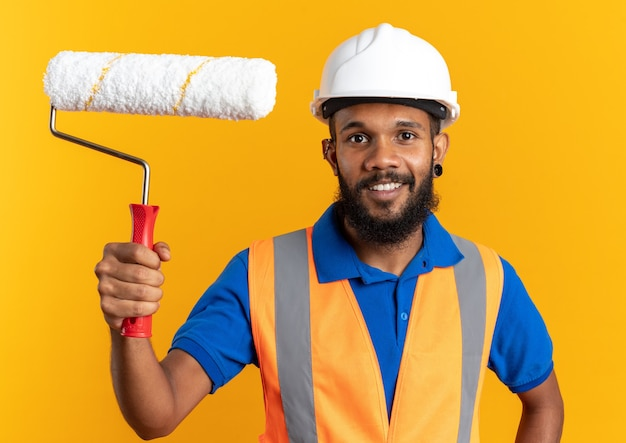 Sorridente giovane costruttore afro-americano uomo in uniforme con casco di sicurezza che tiene rullo di vernice isolato su sfondo arancione con copia spazio